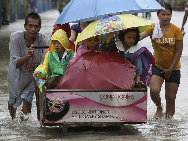 A man pushes a cart full of schoolchildren as they cross a flooded road in suburban Pasig, east of Manila, Philippines, Wednesday Aug. 15, 2012. A second tropical storm in as many weeks battered the northern Philippines on Wednesday as forecasters warned that the still-reeling capital could see more flooding.  Photo: Aaron Favila, Associated Press / SF