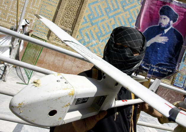 "A militiaman loyal to Iraqi Shiite cleric Moqtada Sadr displays a U.S. military drone on Aug. 22, 2004. The militia claimed to have shot down the drone the previous day. The Arabic writing on the wing of the drone reads: ""Equipment of the American army."" Photo: AHMAD AL-RUBAYE, AFP/Getty Images / 2004 AFP"