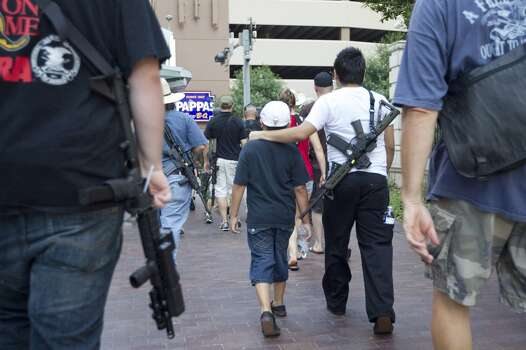"Jr. Velez, 21, puts his arm around his little brother while walking with his AR-15 rifle down Bagby, as they joined a group of more than 20 people with the pro-gun organization, Come and Take it Houston, as part of a rally to educate people about local gun laws Thursday, July 4, 2013, in Houston.<br /><br /><br /> ""This is a Come and Take it Houston walk to help inform citizens about the gun laws here in Texas,"" co-organizer  Kenneth Lindbloom said. ""In Texas there are no restrictions on the open cary of long arms like rifles and shotguns. We want people to realize that in the hands of good people, guns are not dangerous and they don't kill people. When good people have guns it serves as a deterrent to stop crime.""( Johnny Hanson / Houston Chronicle ) Photo: Houston Chronicle"