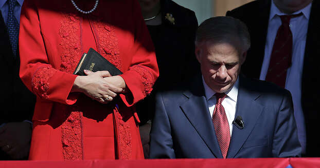 Gov. Greg Abbott, right, bows his head during the benediction as his wife Cecilia Abbott holds the family Bible used in the Inauguration Ceremony of Texas Governor in Austin, Texas.  Tuesday, Jan. 20, 2015. Photo: Bob Owen, San Antonio Express-News / ©2015 San Antonio Express-News