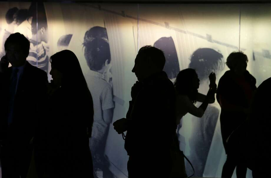 People are silhouetted against a photo of Vietnamese adoptees in an airplane at the opening of an exhibition on Operation Babylift at the Presidio Officer's Club in San Francisco on Thursday, April 16, 2015. The exhibition explores the events of 1975 in which more than 1,500 Vietnamese children traveled through the Presidio to adoptive families in the U.S. during the waning days of the Vietnam war. Adoptees, and people who helped relocate them, came out for the event. Photo: Terray Sylvester, The Chronicle