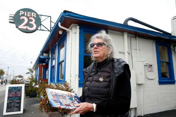 Flicka McGurrin, owner of the Pier 23 Cafe, stands between her restaurant and the Pier 23 shed in San Francisco, Calif. on Wednesday, Nov. 15, 2017. McGurrin is less than thrilled by the prospect of a homeless center opening next door to her business. Supervisor Aaron Peskin is floating an idea to open two homeless navigation centers at Pier 23 and on a parking lot at 88 Broadway.