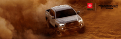 Gray 2020 Toyota Tacoma Kicking Up Dust in the Desert with Red, White and Black Earnhardt Toyota Logo in Upper Right Corner