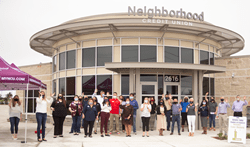 Group of people lined up cheering in front of the new Neighborhood Credit Union building in Anna, TX.