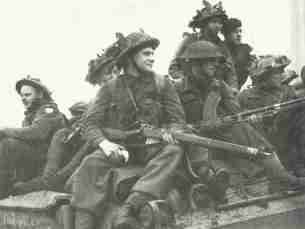 British troops move forward on Sherman tank