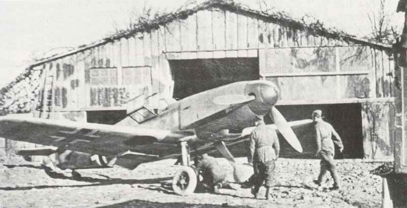 e 109 F is standing outside a hangarette camouflaged as a barn