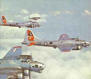 P-51B Mustang escort fighter next to a formation of B-17G