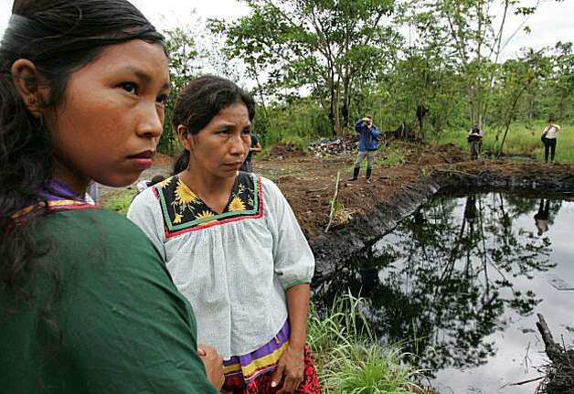 ** FILE ** Cofan indigenous women stand near an open oil pit in the Sucumbios province in Ecuador's Amazon in this Wednesday, Oct. 19, 2005 file photo.  A court-appointed expert recommended on April 2, 2008 that Chevron Corp. pay up to US$16 billion (10.2 billion) for allegedly polluting Ecuador's Amazon in a class-action suit by 30,000 jungle settlers and Indians.  (AP Photo/Dolores Ochoa) Photo: Dolores Ochoa R., Associated Press
