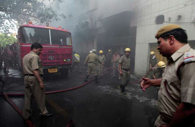 Fire fighters work at the scene, after a fire broke out in a multi-storey building housing the Punjab National Bank at Parliament Street in New Delhi, India, Wednesday. No deaths were reported but some of the injured, who had trouble in breathing, have been taken to hospitals according to local news reports. (AP Photo/Saurabh Das) Photo: Associated Press / SL