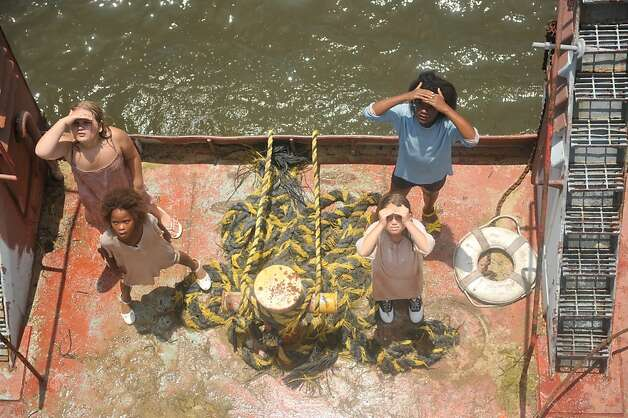 """Quvenzhane Wallis as """"Hushpuppy""""  and the bathtub girls on Sargeant Major's boat on the set of BEASTS OF THE SOUTHERN WILD. Photo: Jess Pinkham, Fox Searchlight / SF"""