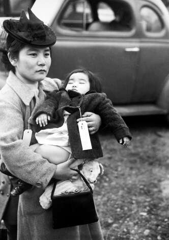 Fumiko Hayashida holds 13-month-old daughter Natalie, while waiting board a ferry from Bainbridge Island to Seattle on March 30, 1942. They were among 227 Japanese Americans forced into interment camps during World War II under Executive Order 9066.  Photo: Seattlepi.com File/MOHAI, -