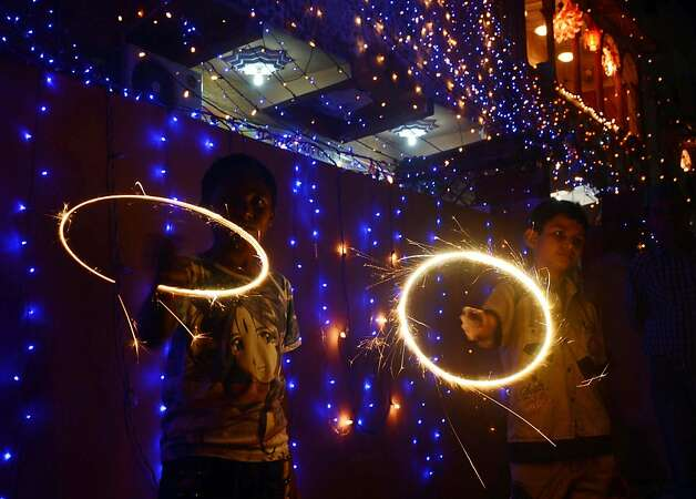 Pakistani Hindu revellers wave sparklers on the occasion of Diwali in Karachi on November 13, 2012. Diwali, the festival of lights, is celebrated with jubilation and enhusiasm as one of the biggest Hindu festivals. People decorate their homes with flowers and Diyas (earthen lamps), celebrate the homecoming of the God Ram after vanquishing the demon king Ravana and honour the Hindu goddess of wealth, Lakshmi. AFP PHOTO/Asif HASSANASIF HASSAN/AFP/Getty Images Photo: Asif Hassan, AFP/Getty Images / SF