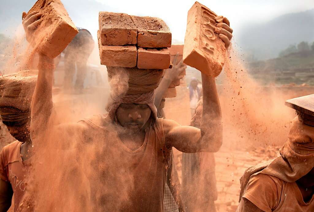 Slaves carry bricks into waiting trucks in 18-hour stretches, at a kiln in Nepal. Photo: Lisa Kristine, Lisa Kristine ©