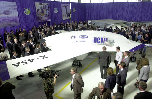 Onlookers move in for a closer look at Boeing's new Unmanned Combat Air Vehicle on September 27, 2000 during an unveiling ceremony at the Boeing Company plant in St. Louis, Mo. Photo: Bill Greenblatt, Getty Images / Getty Images North America