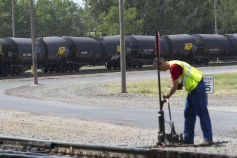 "FILE - In this Aug. 8, 2012 file photo, DOT-111 and AAR-211 class rail tankers pass by on the background as a man works at the Union Pacific rail yard in Council Bluffs, Iowa. DOT-111 rail cars being used to ship crude oil from North Dakota's Bakken region are an ""unacceptable public risk,"" and even cars voluntarily upgraded by the industry may not be sufficient, a member of the National Transportation Safety Board said Wednesday, Feb. 16, 2014. The cars were involved in derailments of oil trains in Casselton, N.D., and Lac-Megantic, Quebec, just across the U.S. border, NTSB member Robert Sumwalt said at a House Transportation subcommittee hearing. (AP Photo/Nati Harnik, File) Photo: Nati Harnik, Associated Press"