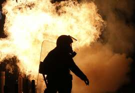 Riot police try to avoid petrol bombs thrown by protesters during clashes in the Athens neighborhood of Exarchia, a haven for extreme leftists and anarchists, on Saturday, Dec. 6, 2014. A march through central Athens to mark the sixth anniversary of the fatal police shooting of an unarmed teenager quickly turned violent Saturday, as marchers damaged store fronts and bus stations, and set fire to clothes looted from a shop. (AP Photo/Petros Giannakouris)
