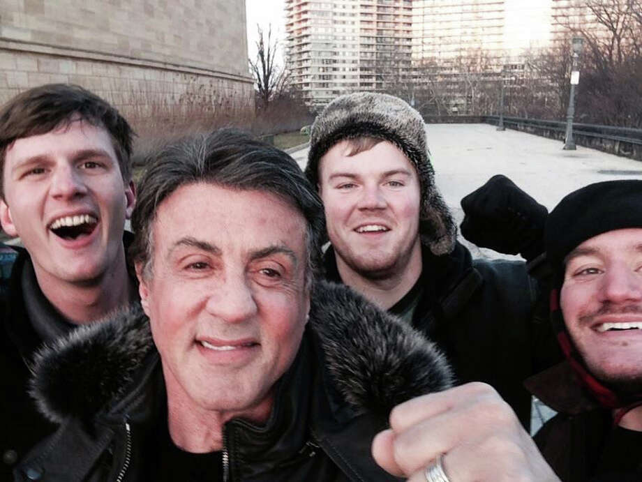 In this Jan. 17, 2015, photo provided by Peter Rowe, Rowe, right, takes a selfie with friends Jacob Kerstan, left, Andrew Wright, third from left and actor Sylvester Stallone in Philadelphia. Rowe said the three friends had just finished racing up the staircase at the city's Museum of Art when they saw Stallone. Stallone made the steps famous in his first turn as fictional boxer Rocky Balboa, who used them as part of his training regimen. Thousands of people now visit the steps each year to re-create the run. Photo: Peter Rowe, AP / AP