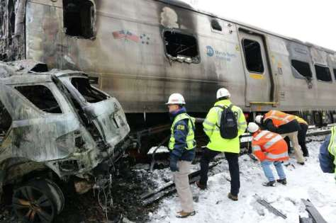 "This February 4, 2015 National Transportation Safety Board (NTSB) board member Robert Sumwalt(L) and other members of the investigation team, view a damaged rail car involved in Metro North train accident in Valhalla, New York. Safety on one of America's busiest commuter rail services was under the spotlight Wednesday after a packed passenger train slammed into a jeep, killing six people north of Manhattan. It was the worst of three deadly crashes in less than two years on the Metro North line that carries around 280,000 passengers a day. The woman driver of a jeep, which became stranded on the tracks, and five rail passengers were killed in the February 3 rush-hour accident, which ripped up tracks and ignited a major explosion. Fifteen other people were injured, seven of them seriously, in what should have been a monotonous but totally safe journey home to the suburbs after a busy working day in America's largest city.  AFP PHOTO / HANDOUT / NTSB    == RESTRICTED TO EDITORIAL USE / MANDATORY CREDIT: ""AFP PHOTO / HANDOUT / NTSB ""/ NO MARKETING / NO ADVERTISING CAMPAIGNS / NO A LA CARTE SALES / DISTRIBUTED AS A SERVICE TO CLIENTS ==--/AFP/Getty Images ORG XMIT: New York Photo: -- / AFP"