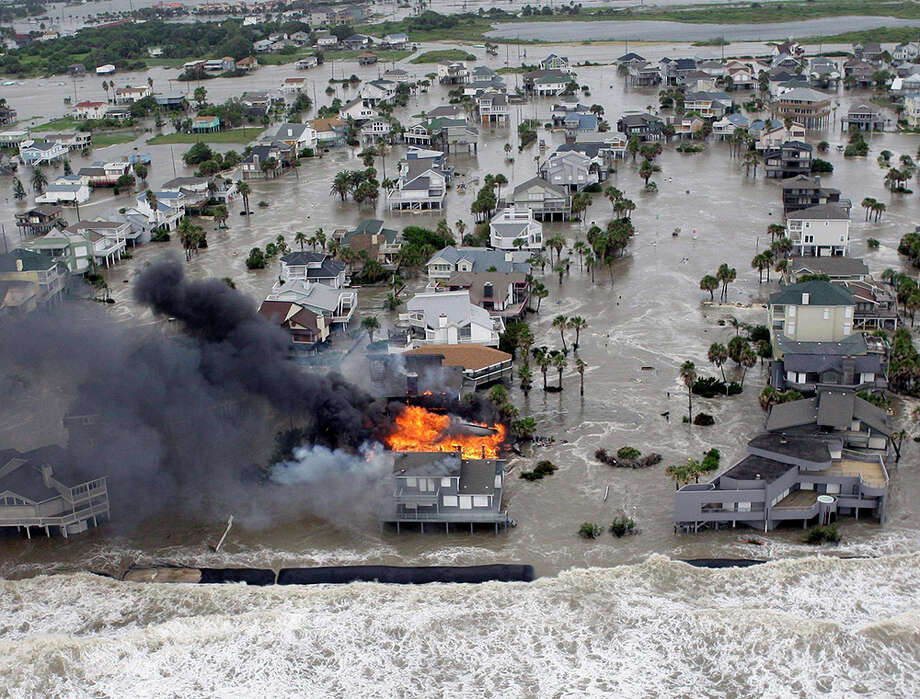This Sept. 12, 2008, file photo shows fire destroying homes along the beach on Galveston Island as Hurricane Ike approaches. Photo: David J. Phillip, Chronicle Files, Beaumont Enterprise Files, University Of Houston Libraries Special Collections, AFP/Getty Images, The Associated Press / AP