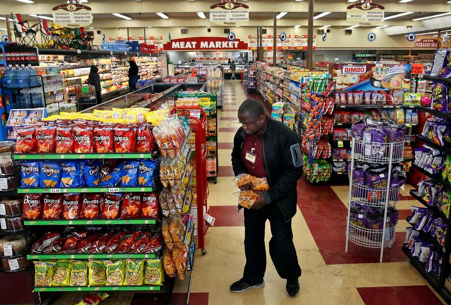 Manager Wallace Miles stocks shelves at Gazzali's in East Oakland. The market has recently added online ordering and delivery. Photo: Leah Millis, The Chronicle