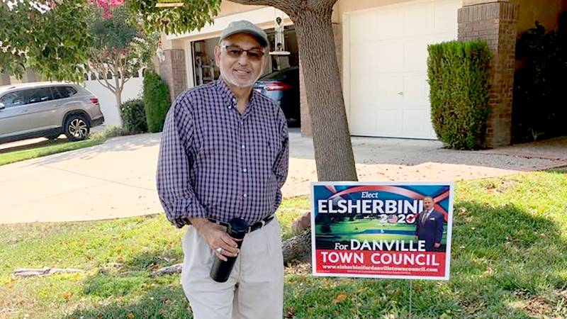 Muhammed Jawaid, an immigrant from Pakistan, poses in front of his Danville home by a yard sign supporting his friend Mohamed Elsherbini's campaign for Danville town council.