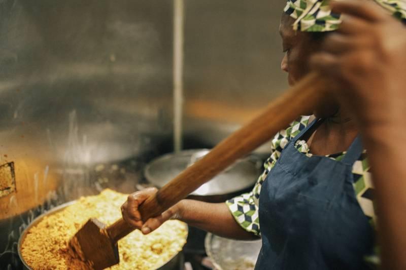 Ruth Ogbe's mother, Maria Ejuwa, prepares Jollof rice at the family run Nigerian restaurant.