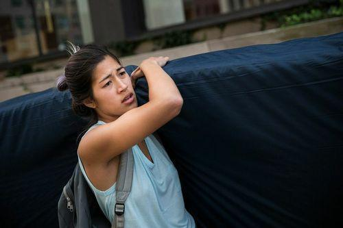 "Columbia University senior Emma Sulkowicz carries her mattress on campus as part of her senior thesis, a performance art piece called ""Carry That Weight."""