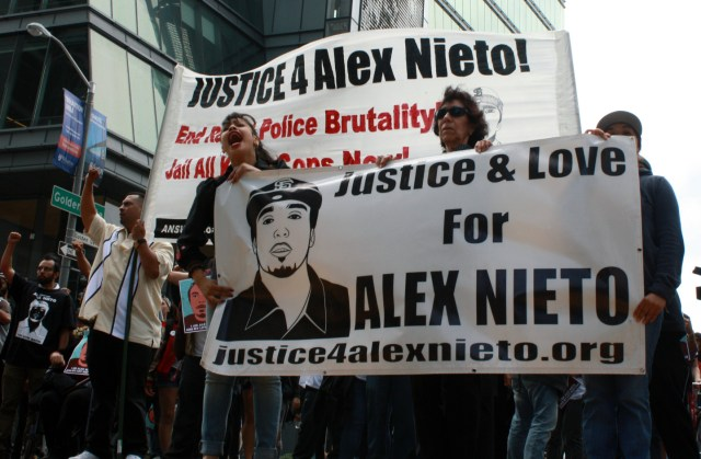 Alejandro Nieto's mother Elvira Nieto (center) leads an Aug. 22 march to announce the filing of a lawsuit against the city over the fatal shooting of her son. (Alex Emslie/KQED)