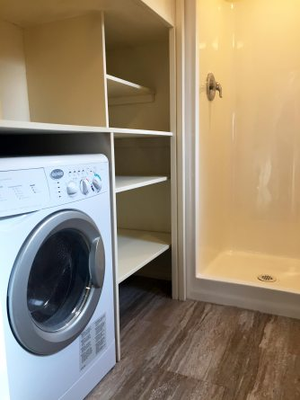 A shower stall and washing machine inside a 'tiny house' parked in front of Fresno City Hall.