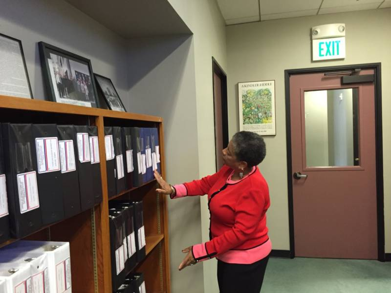 OCC Executive Director Joyce Hicks peruses binders filled with complaint summary reports.