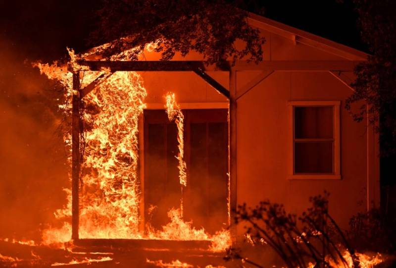 Flames overtake a structure as nearby homes burn in the Napa wine region in California on October 9, 2017, as multiple wind-driven fires continue to whip through the region.