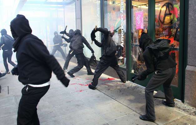 Black-clad protesters break windows on downtown businesses including American Apparel and NikeTown during a May Day rally on Tuesday, May 1, 2012 in downtown Seattle. Photo: JOSHUA TRUJILLO / SEATTLEPI.COM