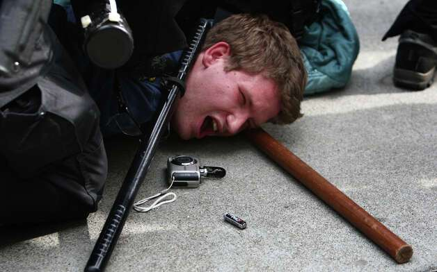 A man that was seen hitting an officer in his face shield with a glass jar is taken down by officers during a May Day rally on Tuesday, May 1, 2012 in downtown Seattle. The rally turned violent when black-clad protesters smashed windows and threw objects at police. One officer was hit in the head with a glass bottle. Photo: JOSHUA TRUJILLO / SEATTLEPI.COM