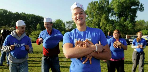 Matt Smith of Clinton Township carries his bounty at the Coney drop at H.Y.P.E. Recreation Center field in Dearborn Heights on Wednesday in Dearborn Heights, Mich. Contestants will have 95 seconds to gather as many as they can. The dogs will then be donated to a local dog rescue charity for food. (AP Photo/Detroit News, David Coates) Photo: Associated Press / SL