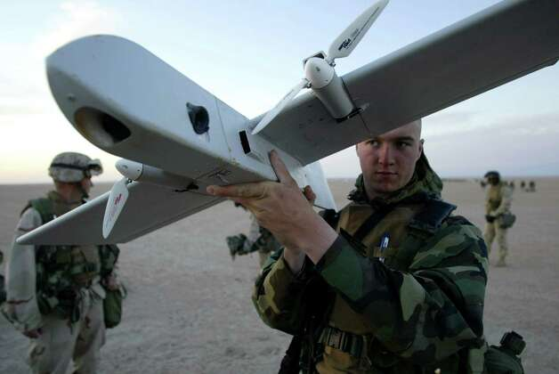 U.S. Marines watch a demonstration of the Dragon Eye drone on February 16, 2003, in Kuwait. The drone can fly over enemy lines for one hour, sending back infrared real time images. Photo: Robert Nickelsberg, Getty Images / Robert Nickelsberg