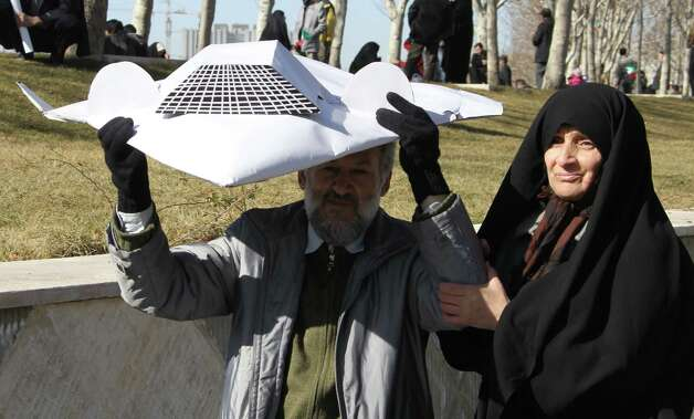 An Iranian couple hold a model of the captured US RQ-170 drone during the 33rd anniversary of the Islamic revolution in Azadi (Freedom) square in Tehran on February 11, 2012. Photo: ATTA KENARE, AFP/Getty Images / 2012 AFP