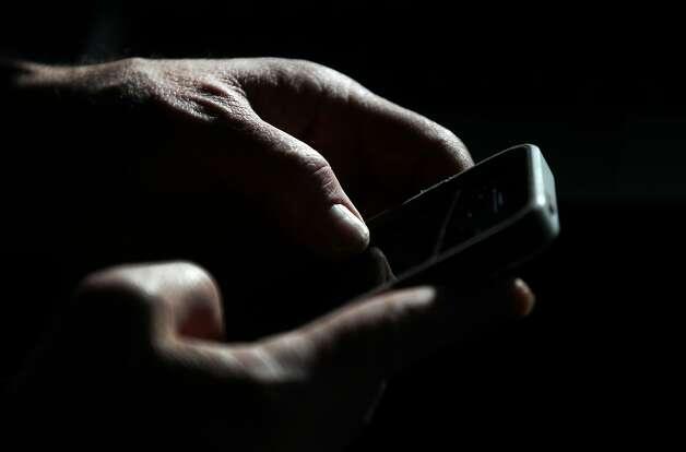 Bret Bocook dice muchas horas de hablar por celular condujeron a su tumor cerebral.  Ahora, él no trae el teléfono a la oreja.  Foto: Leah Millis, La crónica