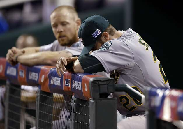 Oakland Athletics' Eric Sogard, left, and Brandon Moss sit in the dugout after the Athletics lost 9-8 to the Kansas City Royals in 12 innings in the AL wild-card playoff baseball game Tuesday, Sept. 30, 2014, in Kansas City, Mo. (AP Photo/Jeff Roberson) Photo: Jeff Roberson, Associated Press