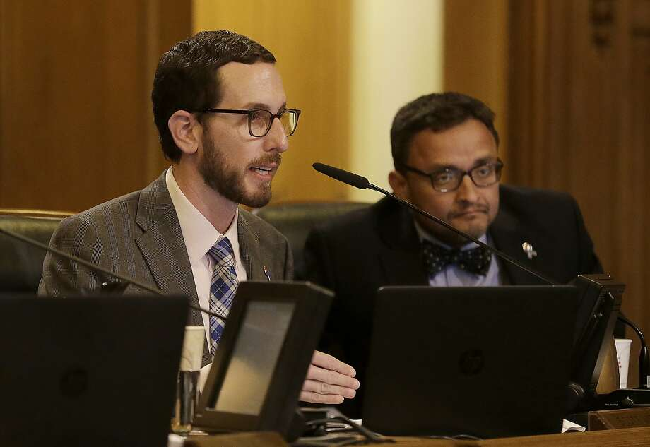 Scott Wiener, left, speaks next to David Campos during a San Francisco Board of Supervisors meeting at City Hall in San Francisco, Tuesday, April 5, 2016. San Francisco has approved a measure making it the first place in the nation to require businesses to provide fully paid leave for new parents. (AP Photo/Jeff Chiu) Photo: Jeff Chiu, AP