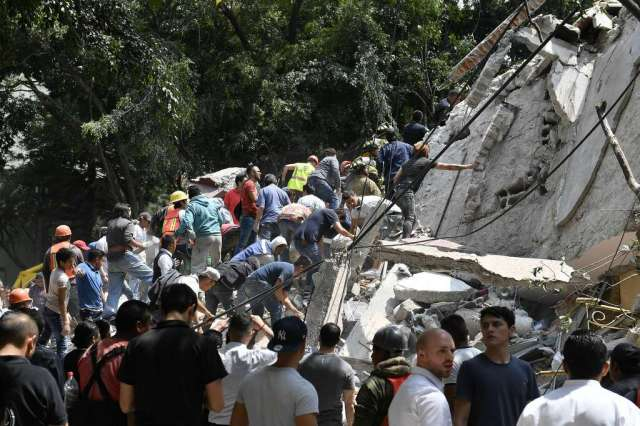 People remove debris of a collapsed building looking for possible victims after a quake rattled Mexico City on September 19, 2017. A powerful earthquake shook Mexico City on Tuesday, causing panic among the megalopolis' 20 million inhabitants on the 32nd anniversary of a devastating 1985 quake. The US Geological Survey put the quake's magnitude at 7.1 while Mexico's Seismological Institute said it measured 6.8 on its scale. The institute said the quake's epicenter was seven kilometers west of Chiautla de Tapia, in the neighboring state of Puebla.  Photo: OMAR TORRES/AFP/Getty Images