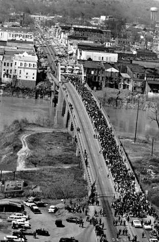 Marchers cross the Alabama river on the Edmund Pettus Bridge at Selma on March 21, 1965.  The civil rights marchers, eight abreast, are led by Dr. Martin Luther King Jr.  This is the start of their five day, 50-mile march to the State Capitol of Montgomery, Alabama.  They are fighting for voter registration rights for blacks, who are discouraged from registering to vote, particularly in small towns in the south.  (AP Photo) / Beaumont