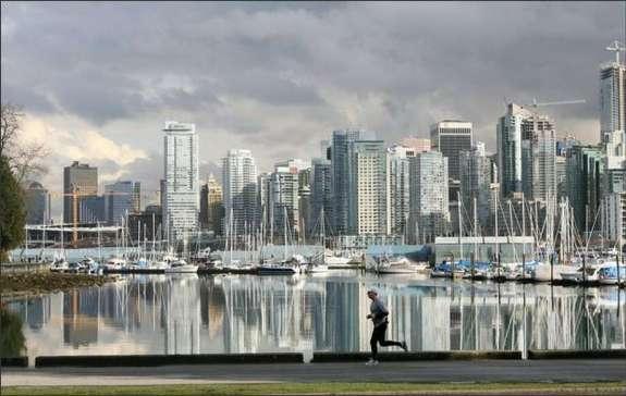Vancouver high-rises loom across the water as a man jogs along Coal Harbor in Stanley Park. Photo: DAN DELONG/P-I