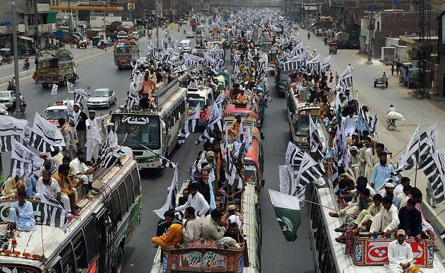 """Activists and supporters of The Defence of Pakistan coalition sit on vehicles in Lahore on July 8, 2012, as they take part in a protest rally to Islamabad.  Pakistan's Islamists who oppose their country's anti-terror alliance with Washington have begun a """"long march"""" to Islamabad to protest over the reopening of a NATO supply route to Afghanistan.  AFP PHOTO/Arif ALIArif Ali/AFP/GettyImages Photo: Arif Ali, AFP/Getty Images / SF"""