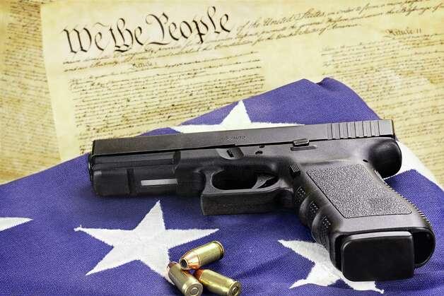 A 45 caliber handgun and ammunition resting on a folded flag against the United States constitution. Photo: Stephanie Frey / Stephanie Frey - Fotolia