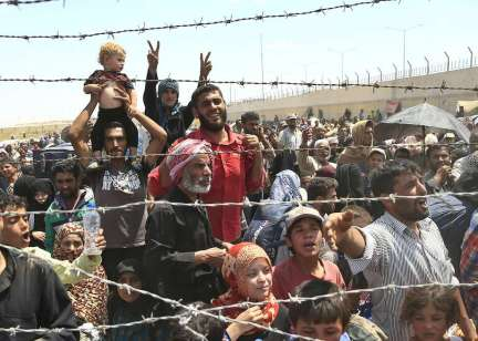 Syrian refugees mass at the Turkish border while they flee intense fighting in northern Syria between Kurdish fighters and Islamic State militants in Akcakale, southeastern Turkey, Monday, June 15, 2015. The flow of refugees came as Syrian Kurdish fighters closed in on the outskirts of a strategic Islamic State-held town on the Turkish border.(AP Photo/Lefteris Pitarakis) Photo: Lefteris Pitarakis, Associated Press