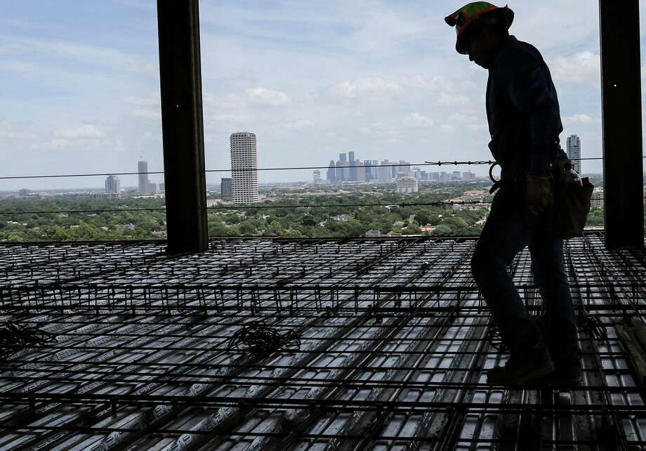 Construction workers work on the penthouses  at 3433 Westheimer Road, photographed on Tuesday, July 5, 2016, in Houston. ( Elizabeth Conley / Houston Chronicle ) Photo: Elizabeth Conley, Staff / © 2016 Houston Chronicle