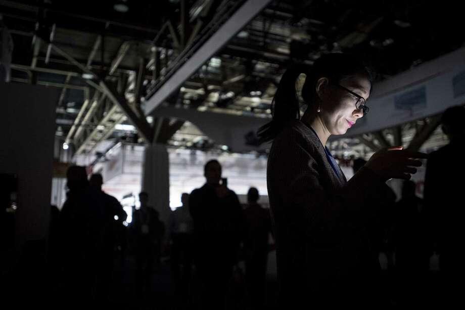 An attendee is illuminated by a mobile device during a power outage at the CES technology event in Las Vegas this past week. Many products at CES want to fill previously unimagined moments of your life with additional stimulation.  Photo: David Paul Morris / © 2018 Bloomberg Finance LP