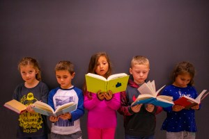 Group of children reading books in class