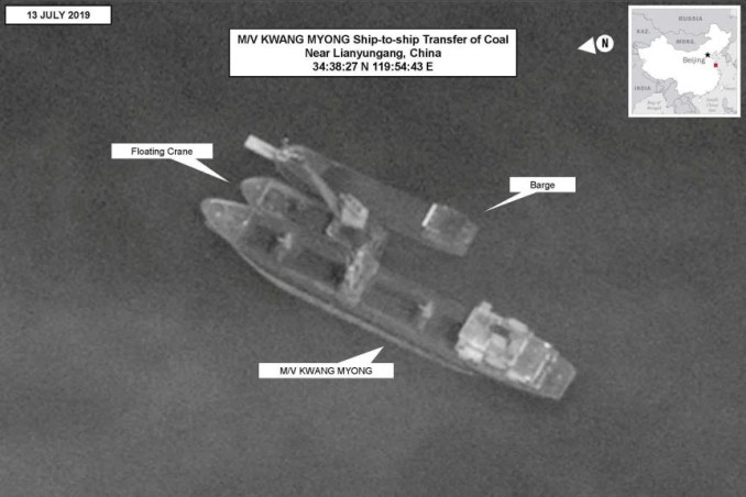 A blakc and white image shows a North Korean-flagged vessel conducting a ship-to-ship transfer of coal.