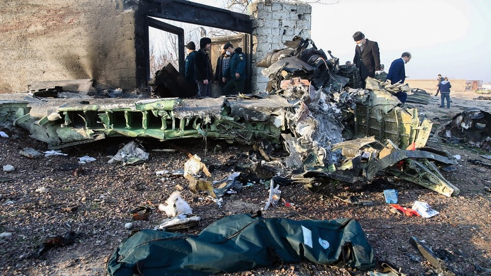 People stand near the wreckage after a Ukrainian plane carrying 176 passengers crashed near Imam Khomeini airport in Tehran on January 8, 2020. All 176 people on board a Ukrainian passenger plane were